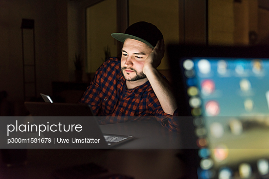 Portrait of freelancer working at night in office - p300m1581679 von Uwe Umstätter