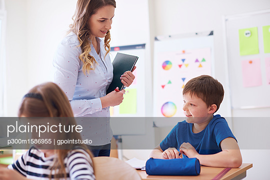 Teacher smiling at schoolboy in class - p300m1586955 von gpointstudio