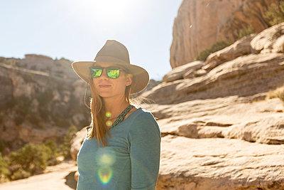 Portrait of woman standing against rock formation - p1166m1210826 by Cavan Images