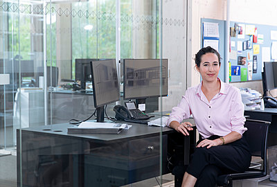 Smiling businesswoman sitting on chair at desk in office - p300m2265177 by Florian Küttler