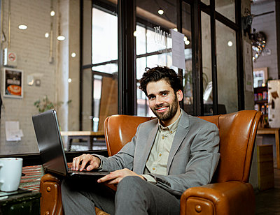 Smiling male professional sitting on armchair with laptop in illuminated cafe - p300m2277370 by Rafa Cortés