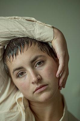 Junge Frau mit der Hand am Kopf - p552m2219772 von Leander Hopf