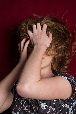 Miserable woman hiding face with hands  - p794m1508037 by Mohamad Itani