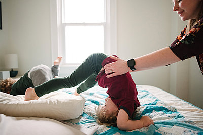Mother helping son tumble in bed - p924m2074216 by Viara Mileva