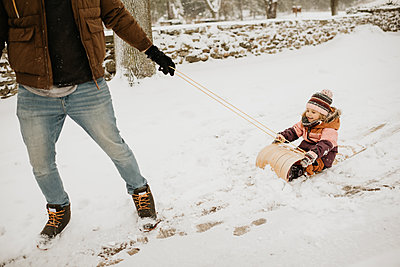 Canada, Ontario, Father pulling daughter (2-3) on toboggan - p924m2271209 by Sara Monika