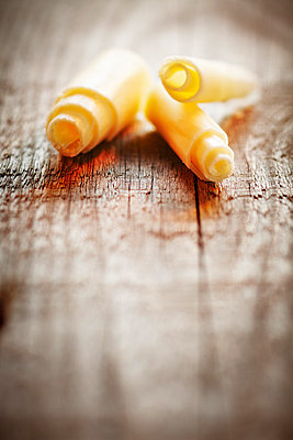 White chocolate curls on a wooden table - p968m658863 by roberto pastrovicchio