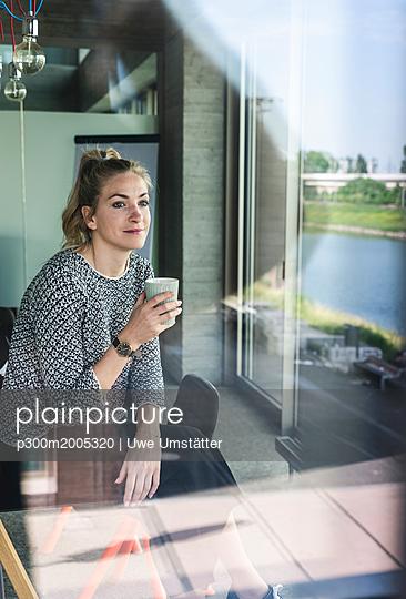 Young woman sitting in office, taking a break, drinking coffee - p300m2005320 von Uwe Umstätter