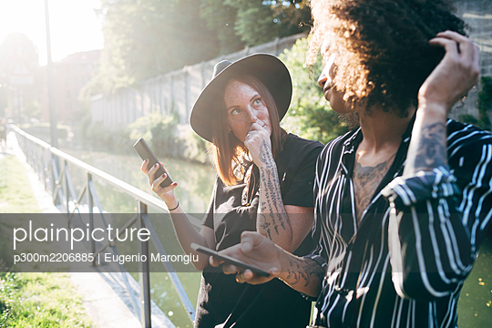 Couple holding mobile phones looking at each other while standing in park - p300m2206885 by Eugenio Marongiu