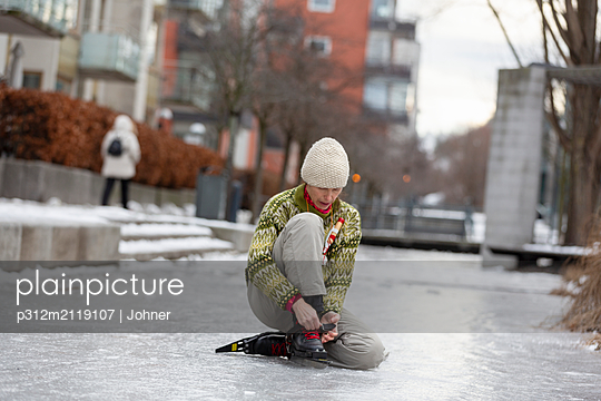 Woman putting ice-skates on - p312m2119107 by Johner