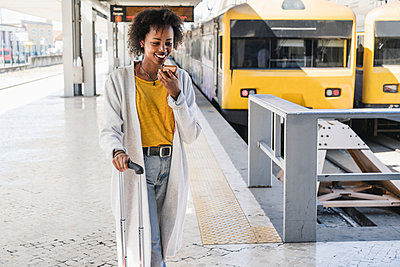 Smiling young woman with earphones using smartphone at station platform - p300m2155843 by Uwe Umstätter