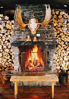 Antlers hanging over fireplace - p312m742353f by Per Eriksson