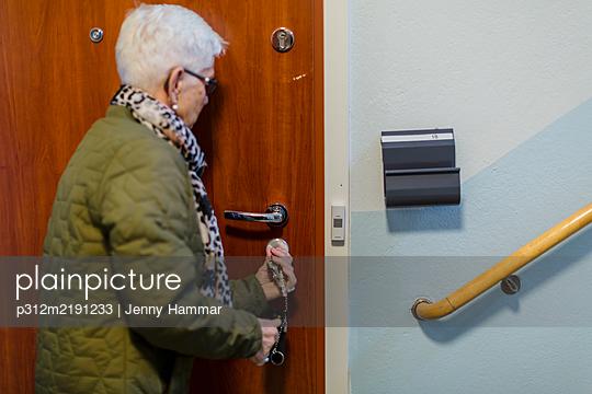 Woman closing entrance door - p312m2191233 by Jenny Hammar