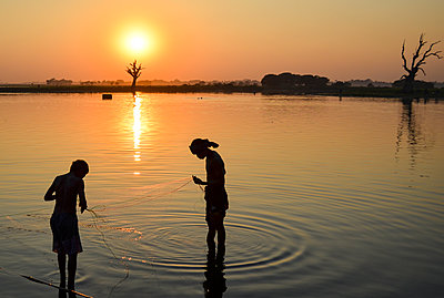 Two boys fishing in a lake at sunset, Amapura, Myanmar. - p1100m2164704 by Mint Images