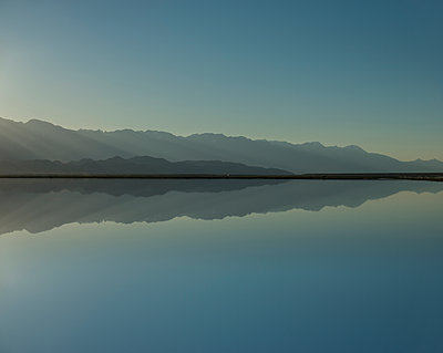 Symmetry view of Mono Lake by mountains against clear sky during sunset - p1166m1526589 by Cavan Images