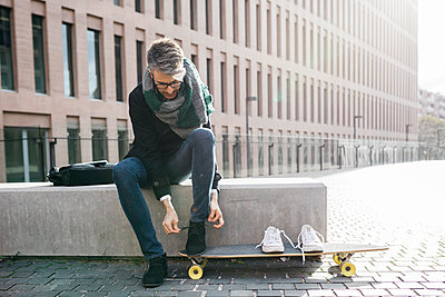 Freelancer with longboard sitting on bench tying his shoes - p300m1549547 by Josep Rovirosa