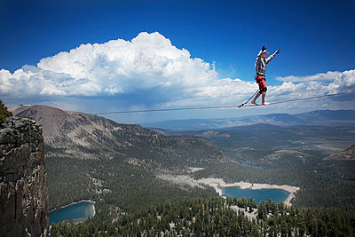 Male highliner in cowboy hat walks a 125 foot highline over a lake in a gap on top of Mammoth Crest  - p343m1003002f by Jared Alden