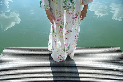 Woman in flower dress on wooden pier - p427m2210853 by Ralf Mohr