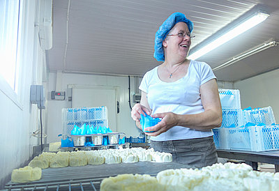 Female cheesemaker looking back while preparing cheeses - p429m2019503 by Seb Oliver