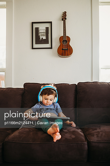 Young boy resting on couch and learning with tablet at home - p1166m2124411 by Cavan Images