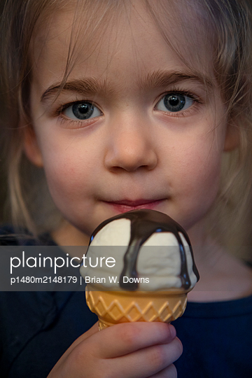 Portrait of a young girl holding a plastic ice cream cone - p1480m2148179 by Brian W. Downs