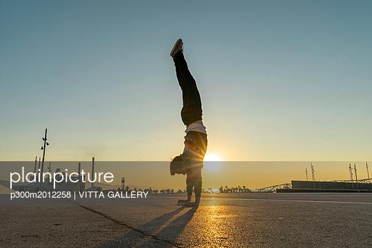 Acrobat doing handstand in the city at sunrise - p300m2012258 von VITTA GALLERY