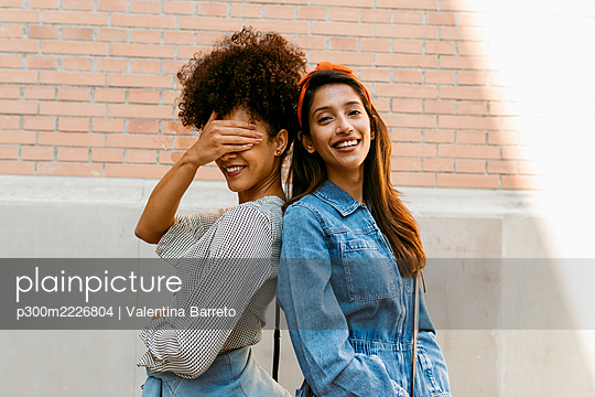 Friend covering eye with hand while standing back to back with woman against wall - p300m2226804 by Valentina Barreto