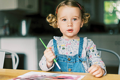 A little girl painting with watercolors at a table - p1166m2201320 by Cavan Images