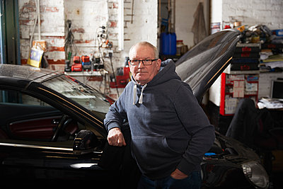 Confident male mechanic with hand in pocket leaning on car at workshop - p300m2276160 by Pete Muller