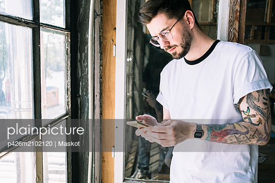 Confident male hipster hacker text messaging through smart phone by window at creative office - p426m2102120 by Maskot