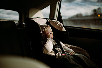 Toddler rubbing her eye, asleep in carseat, driving through city - p1166m2095659 by Cavan Images