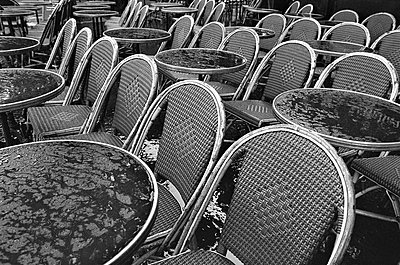 France, Paris, Bistro tables and chairs in the rain - p300m879482 by Tom Hoenig
