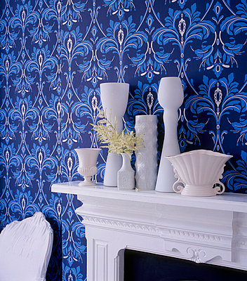 Blue bold patterned wallpaper in a living room with white painted fire surround and white home wares - p349m695242 by Emma Lee