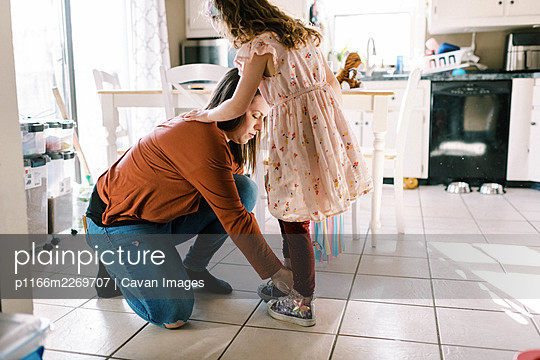 mother helping her daughter put on shoes with laces in kitchen - p1166m2269707 by Cavan Images