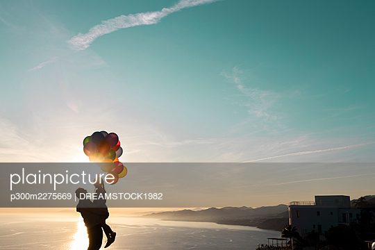 Man in silhouette carrying daughter with balloons by the sea - p300m2275669 by DREAMSTOCK1982