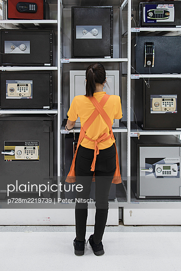 Thailand, Woman in front of wall full of safes - p728m2219739 by Peter Nitsch