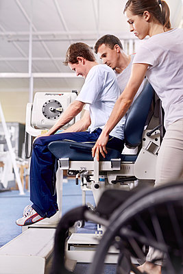 Physical therapists guiding man using equipment - p1023m1121424f by Trevor Adeline