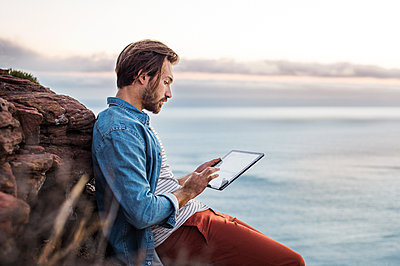 Side view of man using tablet computer by sea - p1166m1142929 by Cavan Images