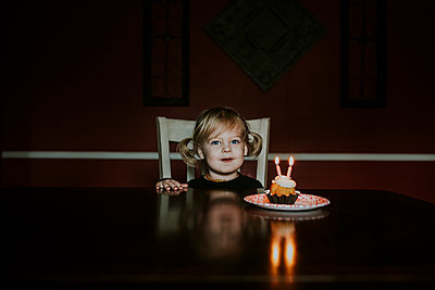 Portrait of cute girl with birthday cake on table at home - p1166m1543909 by Cavan Images