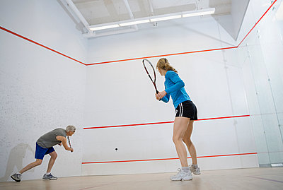 Couple playing squash on court - p1192m1023744f by Hero Images