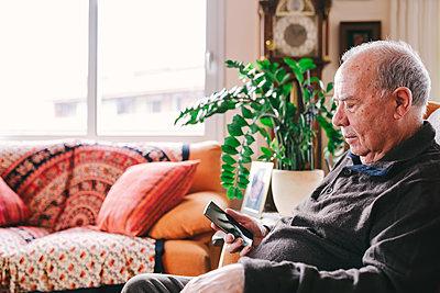 Senior man sitting in the living room  using smartphone - p300m1120463f by Gemma Ferrando