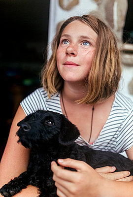 Portrait of freckled girl with black puppy in her arms looking up - p300m2042797 by Marco Govel