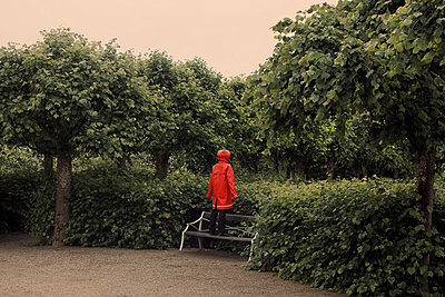 Person wearing raincoat standing on park bench - p312m1076151f by Bruno Ehrs