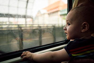 Baby boy gazing out of train window - p795m2160955 by JanJasperKlein