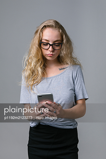 Young woman using smart phone - p1192m2123273 by Hero Images