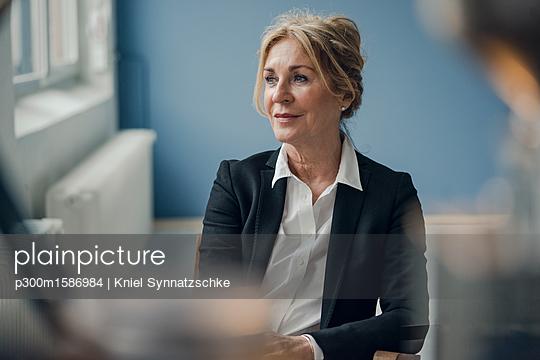 Senior businesswoman sitting on chair looking sideways - p300m1586984 von Kniel Synnatzschke