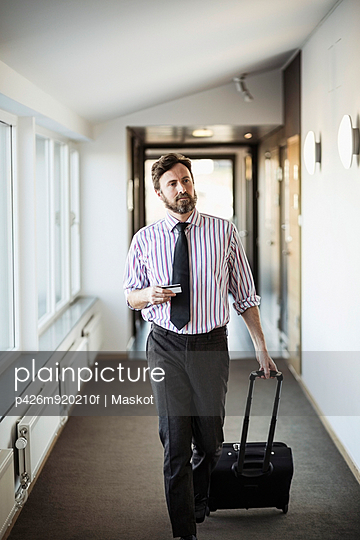 Businessman with suitcase walking in hotel corridor - p426m920210f by Maskot