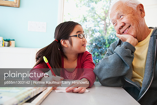 Japanese grandfather helping granddaughter with homework