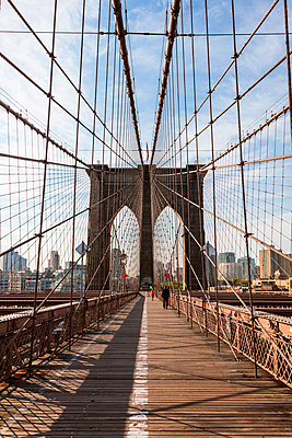 Brooklyn Bridge against sky in New York city during sunny day - p1166m1230526 by Cavan Images