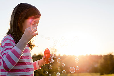 Girl blowing bubbles while standing against clear sky at park during sunset - p1166m1576147 by Cavan Images