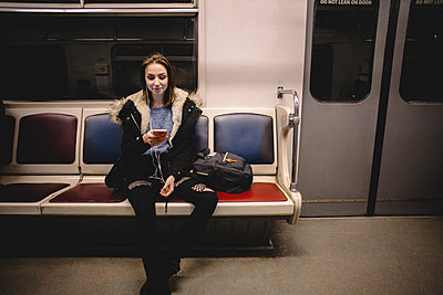 Young happy woman using smart phone while traveling in subway train - p1166m2138129 by Cavan Images